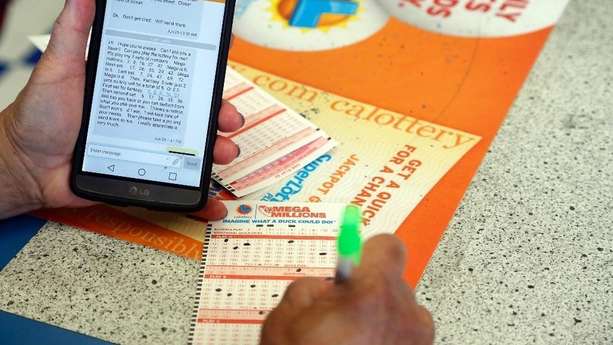 A player fills out lottery slips from texted instructions at Bluebird Liquors in Hawthorne, Calif., Friday afternoon, July 8, 2016. The jackpot for Friday's drawing has soared to over $500 million. (AP Photo/Nick Ut)