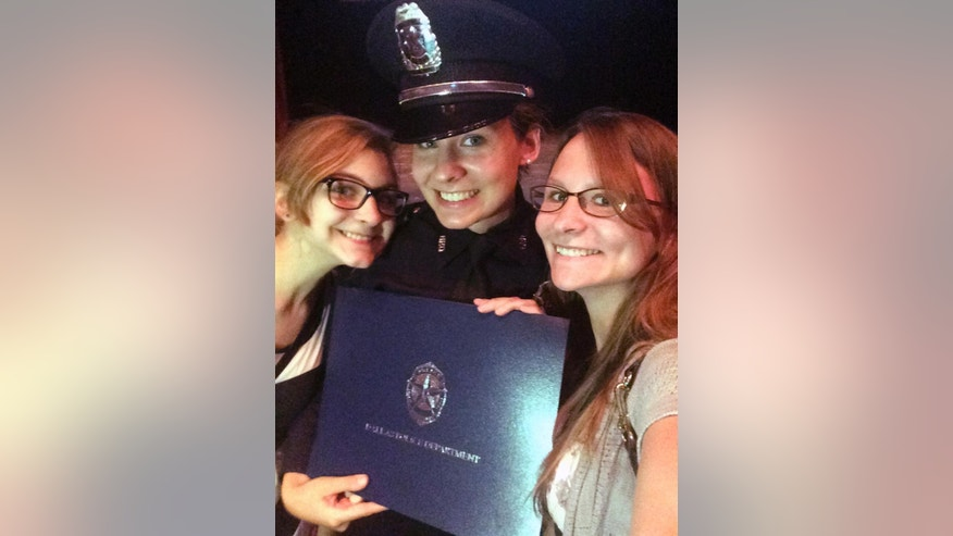 This June 10, 2016, photo provided by Katrina Schwarz shows Gretchen Rocha, center, during her graduation from the police academy at El Centro College in Dallas with her sisters Ingrid Bayer, left, and Katrina Schwartz. Rocha was one of the Dallas police officers who was wounded Thursday, July 7, 2016, when a gunman opened fire on officers in the heart of Dallas during protests over two recent fatal police shootings of black men. Schwartz told The Associated Press on Friday, July 8, that she's been texting with Rocha and her sister told her she wasn't shot but hit by shrapnel. Rocha grew up on a farm just outside Beaver Dam, Wis. (Katrina Schwartz via AP)