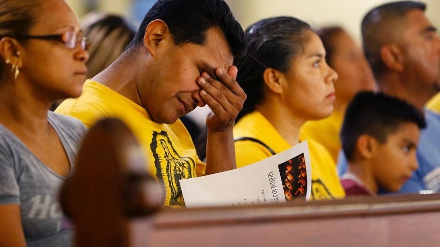 "A worshiper wipes his eyes during a ""United To Heal Prayer Vigil"" at Cathedral Guadalupe, in honor of the Dallas police officers who were slain Thursday, in Dallas, Friday, July 8, 2016. A peaceful protest in Dallas over the recent videotaped shootings of black men by police turned violent Thursday night as gunman Micah Johnson shot at officers, killing five and injuring seven, as well as two civilians. (AP Photo/Gerald Herbert)"