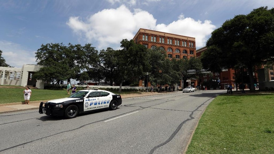 A Dallas patrol car passes Dealey Plaza in front of the Texas School Book Depository building, Saturday, July 9, 2016, in Dallas. After five police officers were killed in a shooting Thursday, a city forever haunted by the assassination of John F. Kennedy is trying to not let the worst America attack on police since Sept. 11 define it again. (AP Photo/Eric Gay)