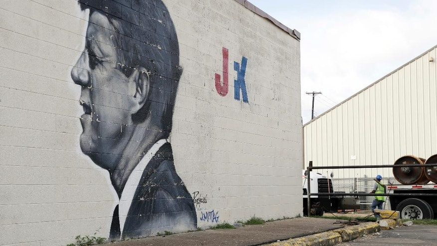 A man works near a mural of President John F. Kennedy, Saturday, July 9, 2016, in Dallas. After five police officers were killed in a shooting Thursday, a city forever haunted by the assassination of John F. Kennedy is trying to not let the worst America attack on police since Sept. 11 define it again. (AP Photo/Eric Gay)