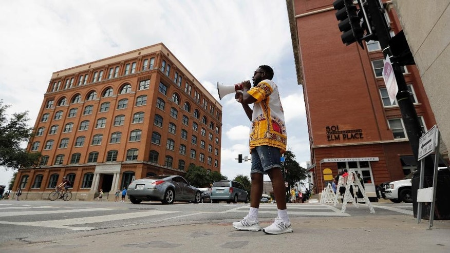 Gregory Bernard Smith, who supports Black Lives Matter, stands near Dealey Plaza as he denounces the killing of five police officers, Saturday, July 9, 2016, in Dallas. After five police officers were killed in a shooting Thursday, a city forever haunted by the assassination of John F. Kennedy is trying to not let the worst America attack on police since Sept. 11 define it again. (AP Photo/Eric Gay)