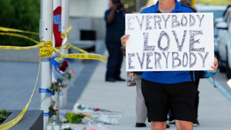 "Chris Bailey walks by a makeshift memorial on Griffin Street holding a sign that reads, ""Everybody Love Everybody"", Friday, July 8, 2016, in Dallas. (AP Photo/Tony Gutierrez)"