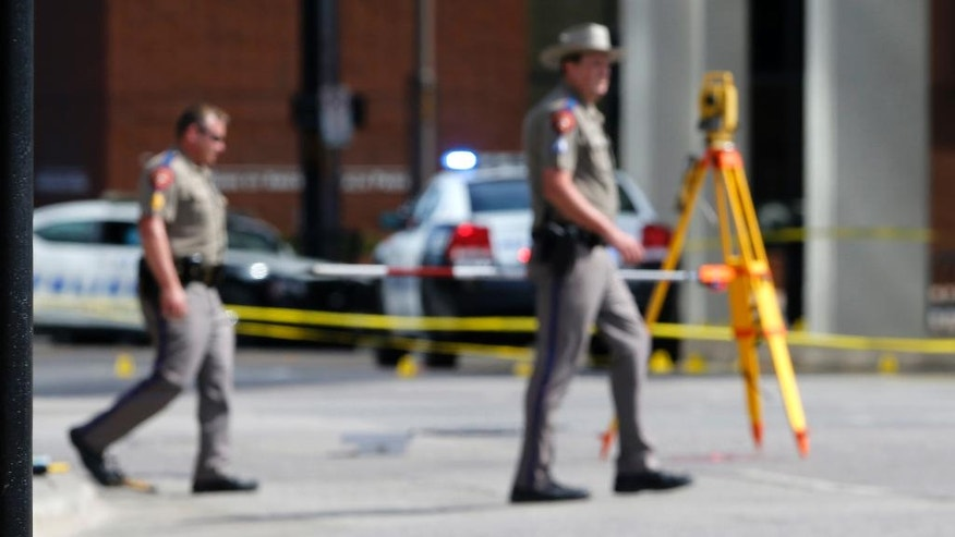 Law enforcement personnel walk near evidence markers at the scene of the police shootings in Dallas, Friday, July 8, 2016. Five police officers are dead and several injured following a shooting during what began as a peaceful protest in the city the night before.  (AP Photo/Gerald Herbert)