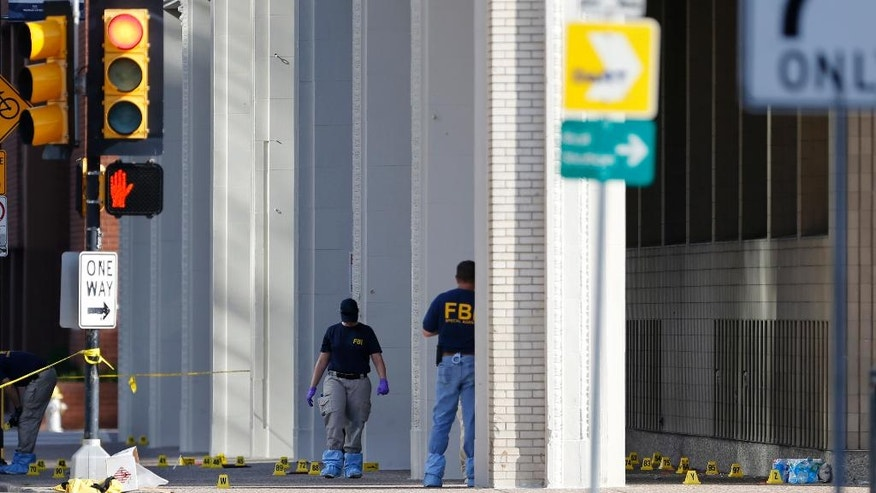 An FBI evidence response team works at the scene of the police shootings in Dallas, Friday, July 8, 2016. Five police officers are dead and several injured following a shooting during what began as a peaceful protest in the city the night before.  (AP Photo/Gerald Herbert)
