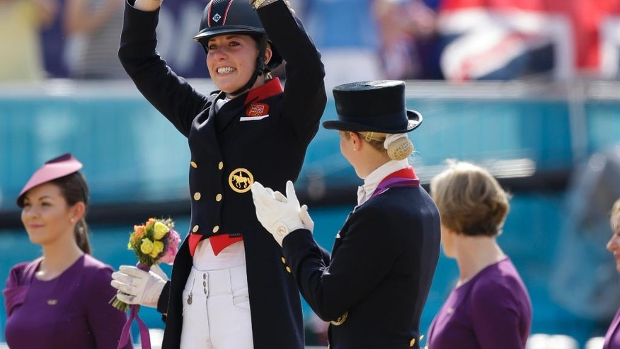 FILE - A Thursday, Aug. 9, 2012 photo from files of gold medal winner Charlotte Dujardin of Great Britain waving as she arrives for the medal ceremony of the equestrian dressage individual competition, at the 2012 Summer Olympics, in London. Charlotte Dujardin is the most successful British dressage rider in the history of the sport and dominates the discipline. The 30-year-old has won all major titles in the sport, including gold in the individual and team events at London 2012. (AP Photo/Markus Schreiber, File)