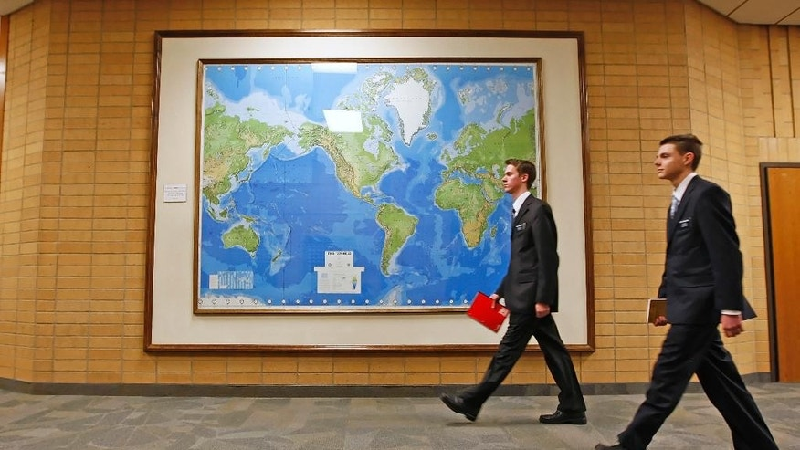 FILE- In this Jan. 31, 2008, file photo, two Mormon missionaries walk past a large map of the world in a hallway at the Missionary Training Center in Provo, Utah. Mormon missionaries will remain in Russia despite the country's new anti-terrorism law, which will put greater restrictions on religious work starting later this month. In a statement issued Friday, July 8, 2016, the Church of Jesus Christ of Latter-day Saints said that missionaries will respect a measure that Russian President Vladimir Putin signed into law this week. (AP Photo/George Frey, File)