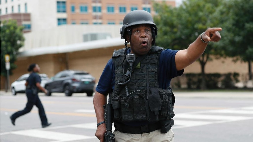A Dallas police officer helps tighten security at their headquarters after receiving an anonymous threat against law enforcement across the city, Saturday, July 9, 2016, in Dallas. Five police were killed and several injured during a shooting in downtown Dallas Thursday night. (AP Photo/Eric Gay)