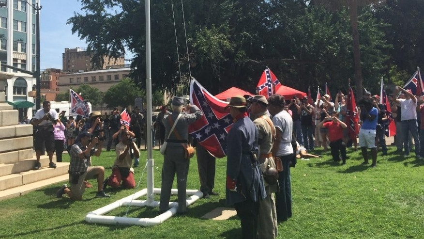 Supporters of the Confederate flag raise it on a temporary flagpole on the grounds of the Statehouse in Columbia, S.C., at a rally on Sunday, July 10, 2016. Counter-protesters showed up but the event was peaceful. (AP Photo/Meg Kinnard)