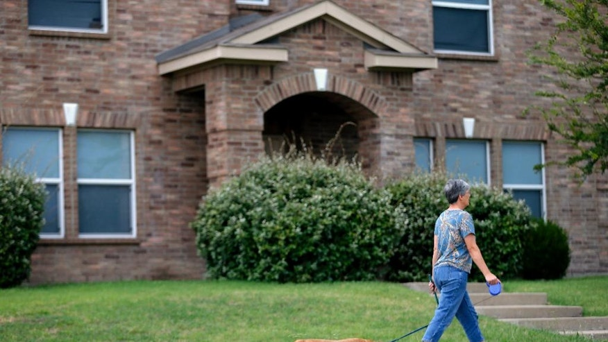 A woman walks her dog past the home where Micah Johnson, the gunman who killed several police officers at a protest march, lived with his mother Saturday, July 9, 2016, in Mesquite, Texas. On Friday investigators searched the home and removed several bags of evidence.  (AP Photo/Tony Gutierrez)