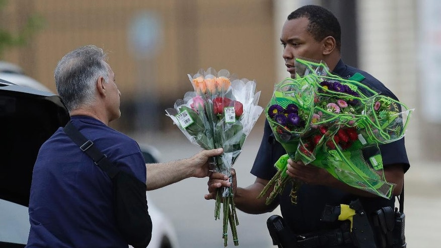 A Dallas police officer receivers flowers at a roadblock outside their headquarters, Saturday, July 9, 2016, in Dallas. A peaceful protest, over the recent shootings of black men by police, turned violent Thursday night as gunman Micah Johnson shot at officers, killing several and injuring others. (AP Photo/Eric Gay)