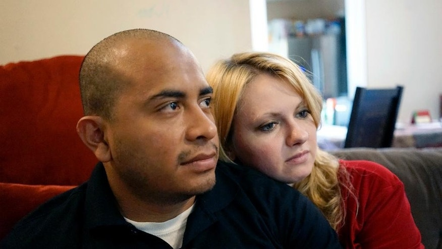 Dallas Police Department Officer Jorge Barrientos, left, is pictured recovering at his home with his girlfriend, Bethany Knutson, Sunday, July 10, 2016, in Dallas. Barrientos was shot in the hand and struck by shrapnel when a gunman attacked officers at a protest against police brutality July 7, 2016. He recounted desperately trying to help fellow officers who were shot, including three from his unit who died. (AP Photo/Christine Armario)