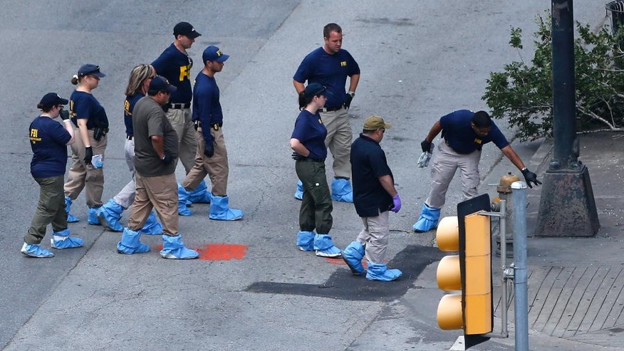 An FBI evidence response team works the crime scene, Sunday, July 10, 2016, where five Dallas police officers were killed Thursday, in Dallas. A peaceful protest over the recent videotaped shootings of black men by police turned violent Thursday night as gunman Micah Johnson shot at officers, killing five and injuring seven, as well as two civilians. (AP Photo/Gerald Herbert)
