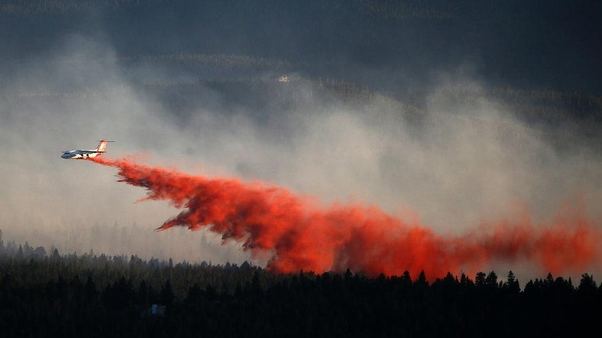 A plane drops retardant while battling the Cold Springs Fire near Nederland, as viewed from Sugarloaf, Colo., Sunday, July 10, 2016. Fire authorities are warning that shifting high winds and high temperatures could put homes in danger. The fire that started on Saturday spread quickly. (AP Photo/Brennan Linsley)