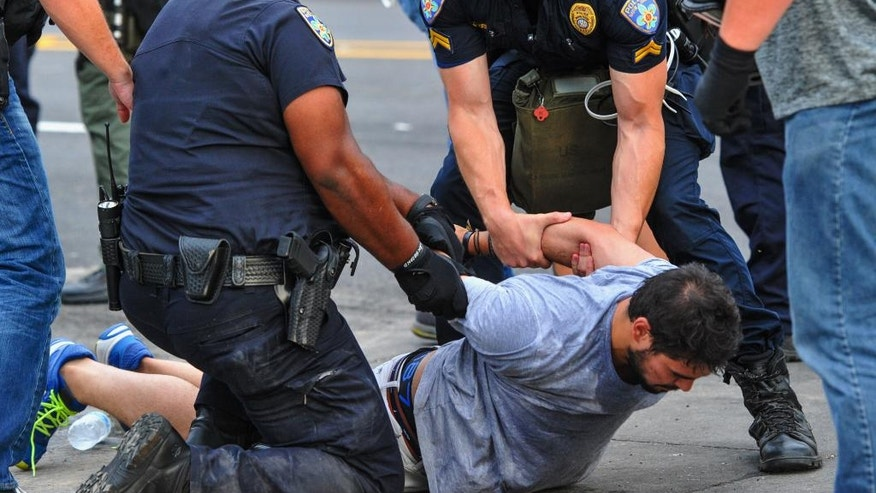 Police officers detain a protester as they try to clear streets while protesters were gathering against another group of protesters in Baton Rouge, La., Sunday, July 10, 2016. Police officers responded to reports that protesters were en route to block Interstate 10 and prevent another group of protesters from marching. (Scott Clause/The Daily Advertiser via AP)