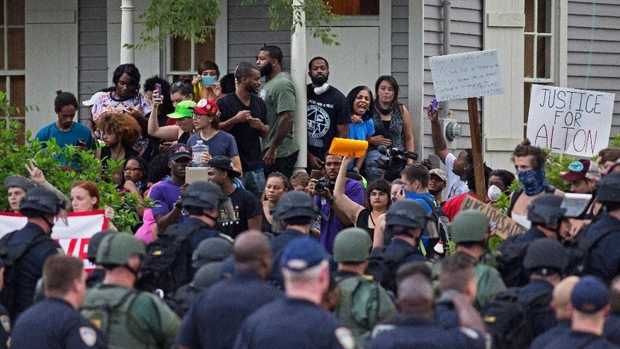 Police march toward protesters in a residential neighborhood in Baton Rouge, La. on Sunday, July 10, 2016. After an organized protest in downtown Baton Rouge protesters wondered into residential neighborhoods and toward a major highway that caused the police to respond by arresting protesters that refused to disperse. (AP Photo/Max Becherer)