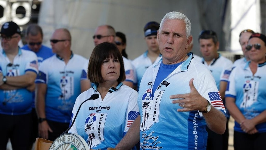Indiana Gov. Mike Pence speaks as his wife Karen, looks on at the opening ceremony for the Cops Cycling for Survivors fundraising bike ride in Indianapolis, Monday, July 11, 2016. Pence is being considered as a possible running mate for GOP presidential nominee Donald Trump, who is expected to decide this week, and the two are expected to attend a fundraiser and rally together Tuesday evening. (AP Photo/Michael Conroy)