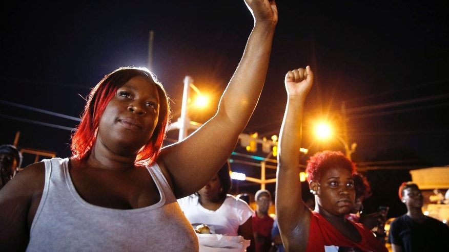 Keilosha Walker, left, of Baton Rouge, puts her fist up during live music at a night rally in honor of Alton Sterling, outside the Triple S Food mart in Baton Rouge, La., Monday, July 11, 2016. Sterling was shot and killed last Tuesday by Baton Rouge police while selling CD's outside the convenience store. (AP Photo/Gerald Herbert)