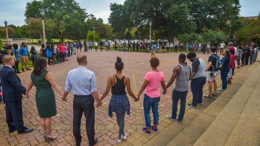 People pray during Prayer Vigil organized by Myron Smothers at Memorial Tower on the Louisiana State University campus in Baton Rouge, La., Monday, July 11, 2016. (Scott Clause/The Daily Advertiser via AP)