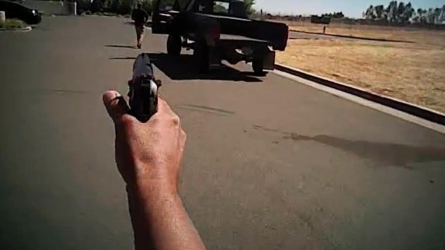 In this image made from a June 25, 2016, police body-camera video released by Fresno Police Department, a police officer points a gun towards Dylan Noble showing his back next to his pickup truck as the officer moves towards Noble walking away from the officer in Fresno, Calif. Fresno police on Wednesday, July 13, released body-camera video of officers fatally shooting Noble, 19-year-old man who ignored repeated commands to stand still and show his hands. (Fresno Police Department via AP)