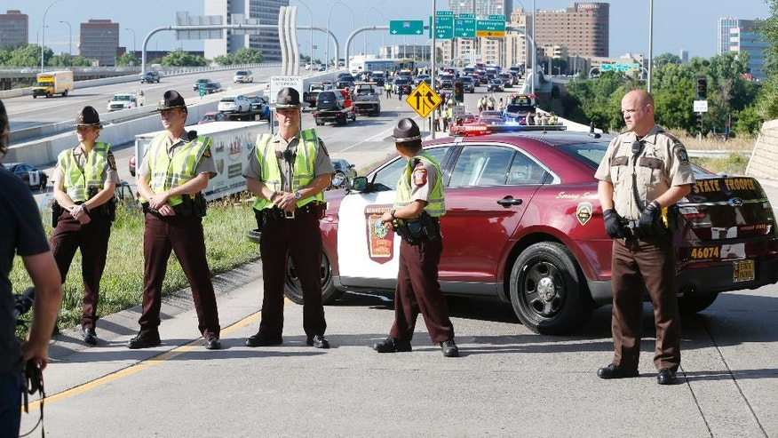State troopers and deputies stand guard at the entrance to the freeway as Interstate 35W is cleared after protesters blocked the highway leading into Minneapolis over the Mississippi River bridge Wednesday, July 13, 2016, as protests continue over the shooting death by police of Philando Castile last week in Falcon Heights, Minn. after a traffic stop by St. Anthony police. The protesters were arrested and removed from the highway. (AP Photo/Jim Mone)