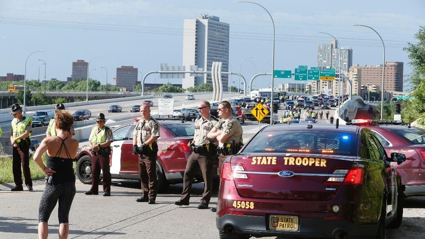 State troopers and deputies stand guard at the entrance to the freeway as Interstate 35W is cleared after protesters blocked the highway leading into Minneapolis over the Mississippi River bridge Wednesday, July 13, 2016 as protests continue over the shooting death by police of Philando Castile last week in Falcon Heights, Minn. after a traffic stop by St. Anthony police. The protesters were arrested and removed from the highway. (AP Photo/Jim Mone)