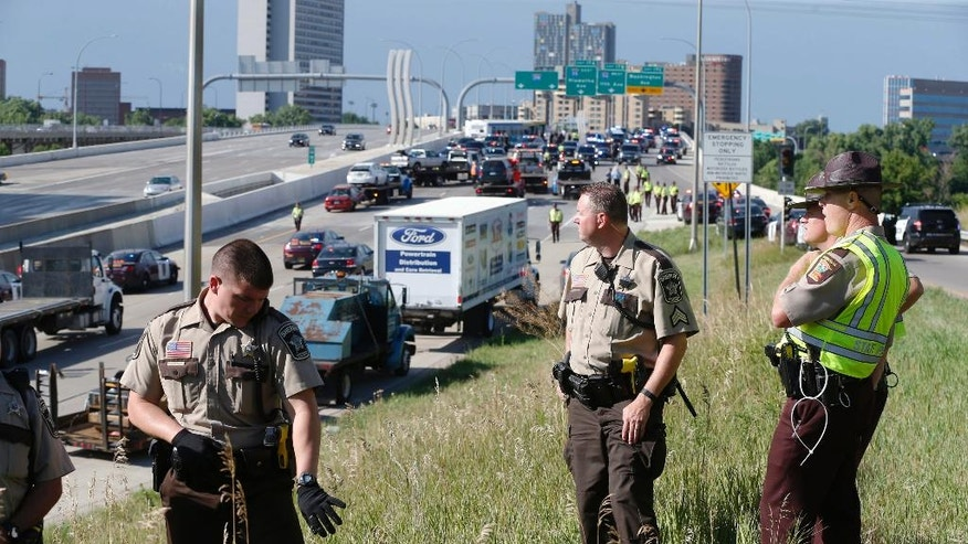 State troopers and deputies stand guard at the entrance to the freeway as Interstate 35W is cleared after protesters blocked the highway bridge over the Mississippi River Wednesday, July 13, 2016, in Minneapolis as protests continue over the shooting death by police of Philando Castile last week in Falcon Heights, Minn. after a traffic stop by St. Anthony police. The protesters were arrested and removed from the highway. (AP Photo/Jim Mone)