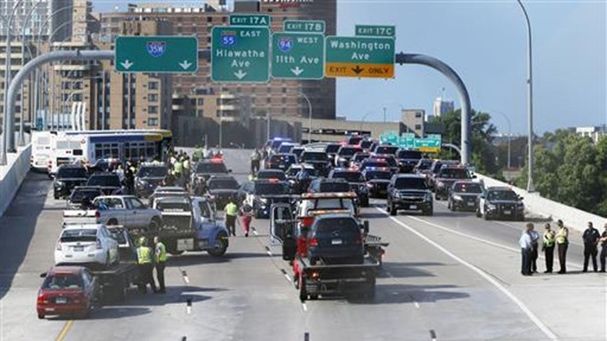 State troopers and police clear the Interstate 35W freeway where protesters blocked the highway leading into Minneapolis over the Mississippi River bridge during rush hour Wednesday, July 13, 2016.