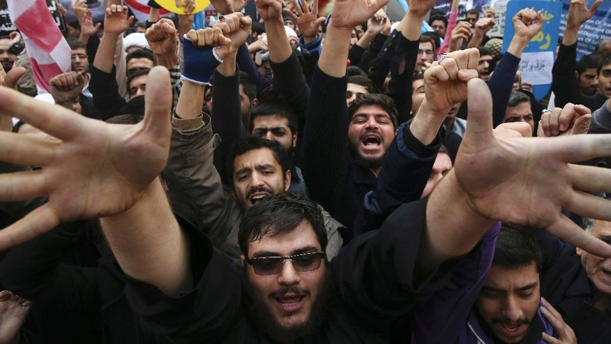 FILE - In this Nov. 4, 2015 file photo, Iranian demonstrators chant slogans during an annual rally in front of the former U.S. Embassy in Tehran. The annual state-organized rally drew greater attention, as Iranian hardliners are intensifying a campaign to undermine President Hassan Rouhani's outreach to the West following a landmark nuclear deal reached with world powers in July. The Iran nuclear accord is fragile at its one-year anniversary. Upcoming elections in the U.S. and Iran could yield new leaders determined to derail the deal. The Mideast's wars pit U.S. and Iranian proxies in conflict, with risks of escalation. Iran's ballistic missiles are threatening American allies in the Arab world and Israel, raising pressure on the United States to respond with force. (AP Photo/Vahid Salemi, File)