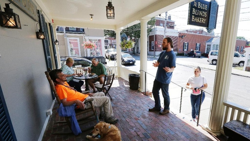 Lev Bryant, manager of the Blue Blinds Bakery, right, engages a customer in a cordial conversation regarding faith on the front porch of the bakery, Wednesday, July 13, 2016, in Plymouth, Mass. The bakery is owned by a Christian sect, The Twelve Tribes. About three weeks ago, messages began to appear on the bakery's Facebook page accusing the sect of child abuse and racism. The group denies the allegations. (AP Photo/Charles Krupa)