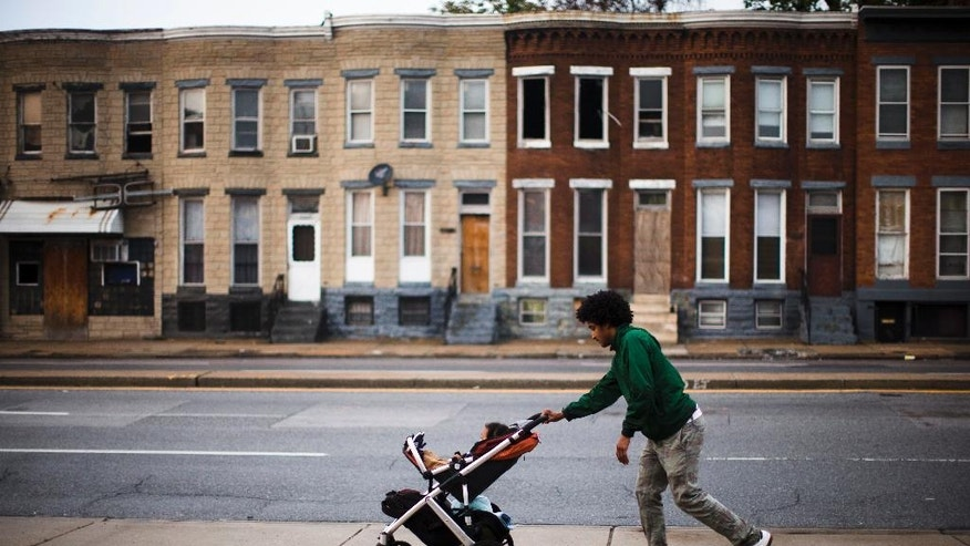"""RACE: Carde Cornish, rides a skateboard as he takes his son, also named Carde, home past blighted buildings in Baltimore on Wednesday, May 11, 2016. Cornish, a young man who has spent his entire life in and around the Baltimore neighborhood where Freddie Gray lived and died, is socially and politicly engaged with the city around him. He works for Taharka Brothers, an ice-cream company with a social mission. """"Our race issues aren't necessarily toward individuals who are white, but it is towards the system that keeps us all down, one, but keeps black people disproportionally down a lot more than anybody else,"""" says Cornish. (AP Photo/Matt Rourke)"""