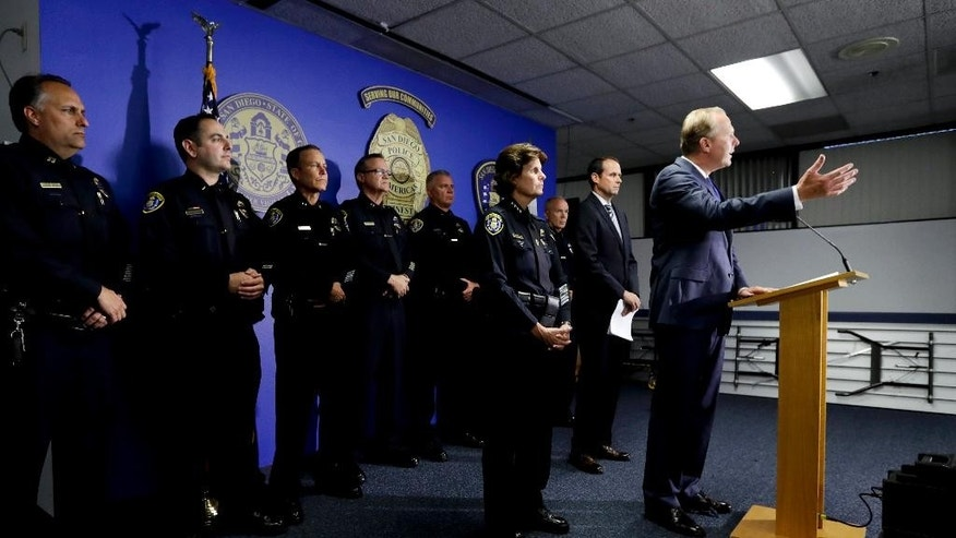 San Diego Mayor Kevin Faulconer, right, speaks at a news conference in front of San Diego Police Chief Shelley Zimmerman, third from right, police Captain David Nisleitand, second from right, and other police officials Friday, July 15, 2016, in San Diego. A fifth transient was attacked Friday shortly before police arrested a man in a series of assaults that have left some victims dead and put San Diego's homeless population on edge. (AP Photo/Gregory Bull)