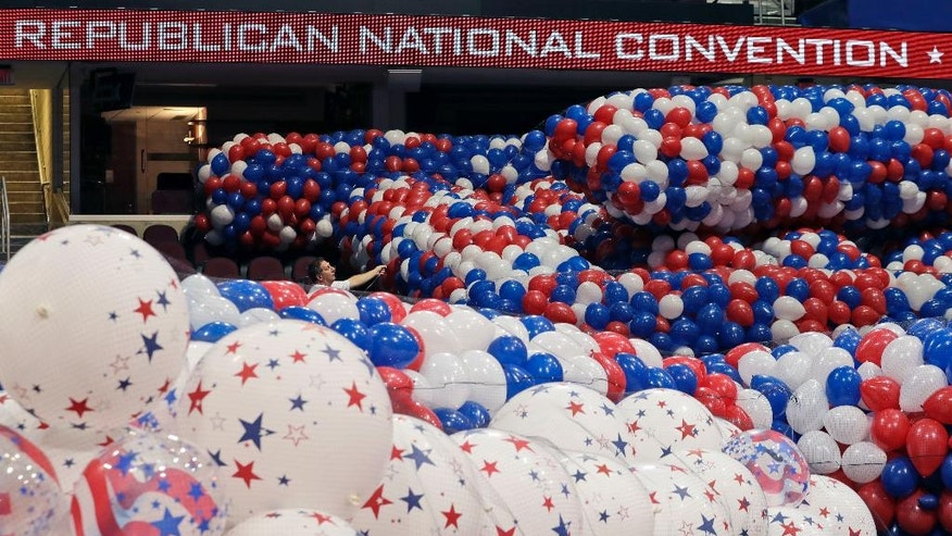 Dave Strnisa, left, moves a bag of balloons as preparations continue for the Republican National Convention, Friday, July 15, 2016, at the Quicken Loans Arena in Cleveland. (AP Photo/Alex Brandon)