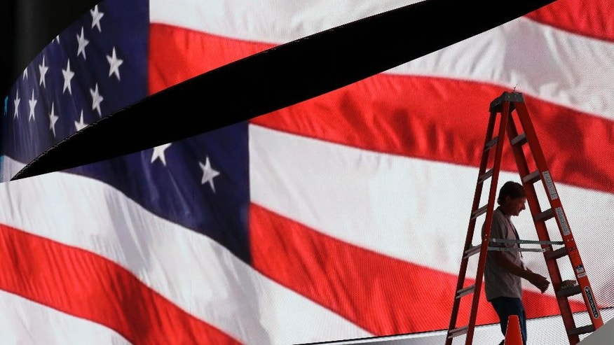 Adam West prepares to move a ladder from in front of the stage screen that displays an American flag as preparations continue for the Republican National Convention, Friday, July 15,2016, at the Quicken Loans Arena in Cleveland. (AP Photo/Alex Brandon)