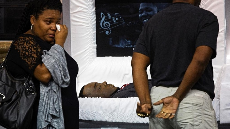 Mourners react after viewing the body of Alton Sterling at the F.G. Clark Activity Center in Baton Rouge, La., Friday, July 15, 2016. Sterling was shot July 5 outside a Baton Rouge convenience store in an encounter with police that was caught on video.  (AP Photo/Max Becherer)