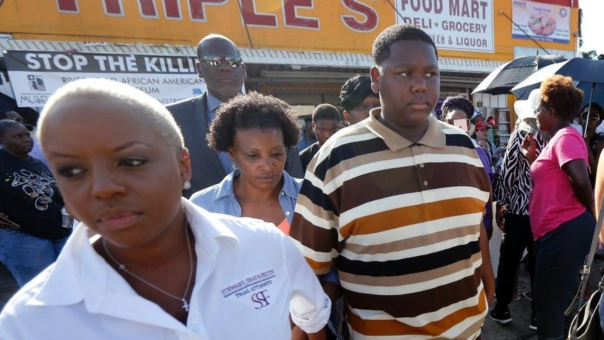 July 13, 2016: Cameron Sterling, center, son of Alton Sterling, who was killed by Baton Rouge police last Tuesday, leaves after speaking to the media outside the the Triple S Food Mart, where his father was killed,in Baton Rouge, La.  Cameron called his father a good man and urged protesters not to resort to violence.