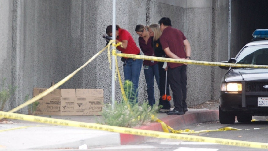 San Diego Police document the scene where a homeless man was attacked Friday, July 15, 2016, in downtown San Diego. San Diego police have detained a person in the investigation of attacks on homeless men that have left three dead. Friday's attack would be the fifth in the series that began July 3. No information about the detained person has been released. (John Gibbins/The San Diego Union-Tribune via AP)