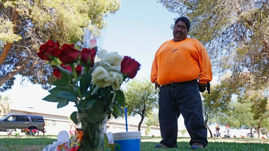 """Margarito Castro, father of Manuel """"Manny"""" Castro Garcia, 19, visits his son's grave at a cemetery Thursday, July 14, 2016, in Phoenix. The teen was killed in June, and is one of a growing number of victims associated with a serial killer according to police. Authorities say all the victims were killed by a thin, lanky man with a handgun who is possibly in his 20s and Hispanic. (AP Photo/Ross D. Franklin)"""