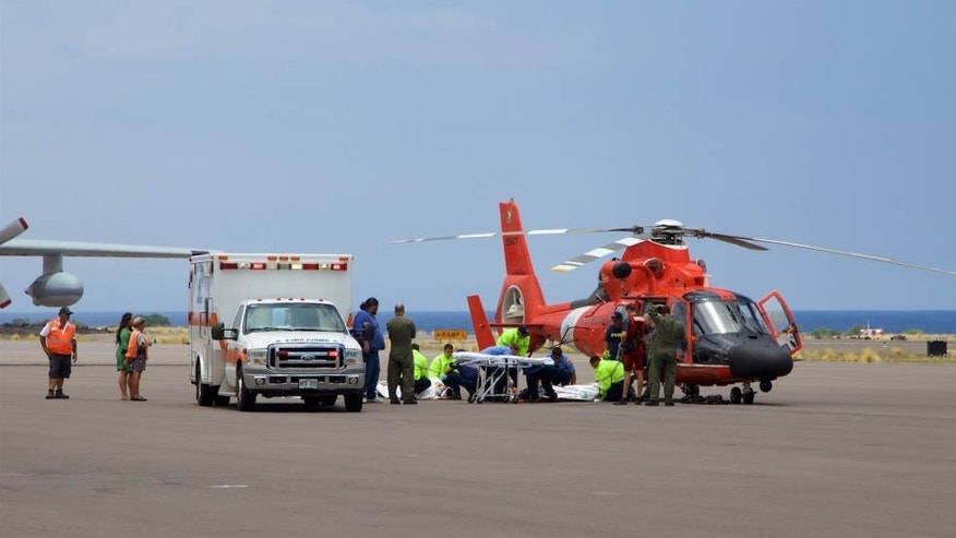 In this photo provided by the U.S. Coast Guard, Coast Guard crews safely deliver David McMahon and Sidney Uemoto to emergency medical personnel in Kona, Hawaii, Friday, July 15, 2016, following their rescue nine miles off Kona.