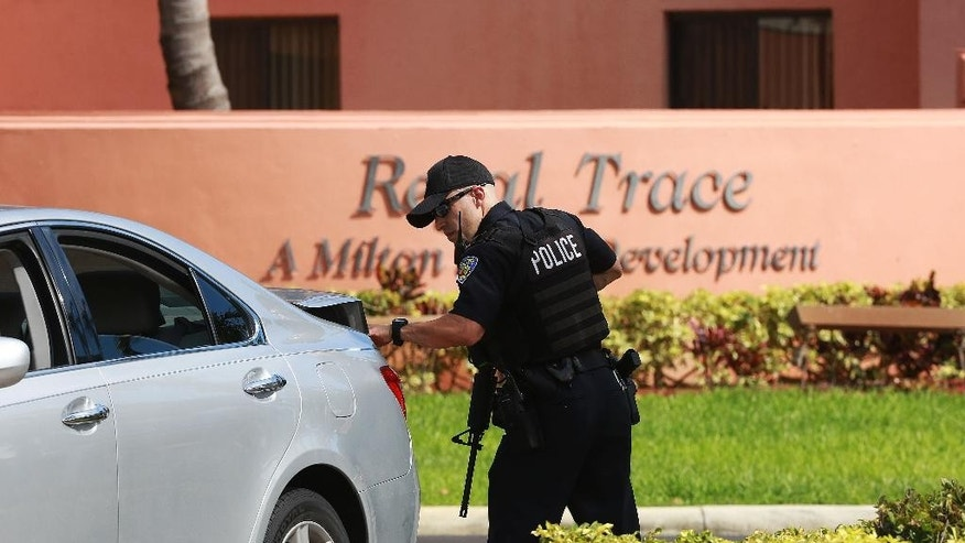 Authorities search Regal Trace apartment complex for Dayonte Resiles after he escaped from the Broward County Courthouse, Friday, July 15, 2016, in Fort Lauderdale, Fla. Resiles, who was awaiting trial for the slaying of a woman whose family founded the Halliburton oil services company, slipped out of his shackles and bolted from a courthouse Friday just before a hearing on whether he could face the death penalty. (Carline Jean/South Florida Sun-Sentinel via AP)