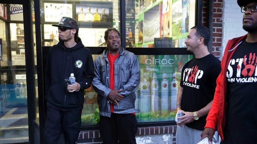 Mike Perry, left, and other members of the Cure Violence group, meet with a resident while patrolling the Stapleton Houses area in the Staten Island borough of New York, Wednesday, June 8, 2016. Their team works to defuse arguments that can lead to shootings and match people with job training and counseling. (AP Photo/Seth Wenig)