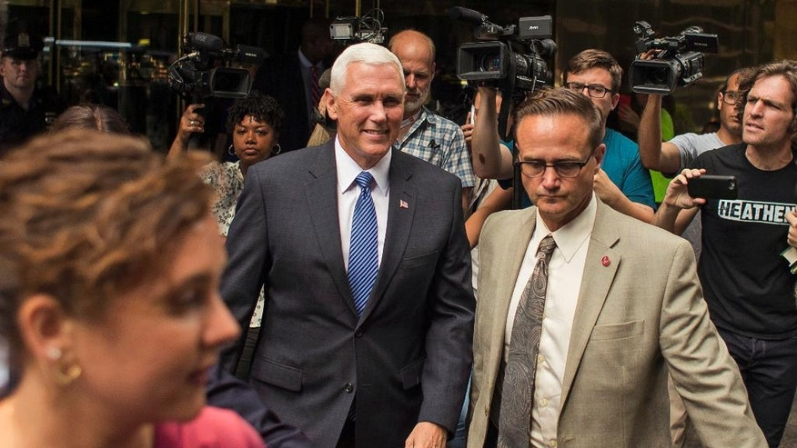 Indiana Gov. Mike Pence, center, leaves after a meeting with Republican presidential candidate Donald Trump at Trump Tower in New York, Friday, July 15, 2016. Trump has chosen Pence as his running mate, adding political experience and conservative bona fides to his Republican presidential ticket. (AP Photo/Andres Kudacki)