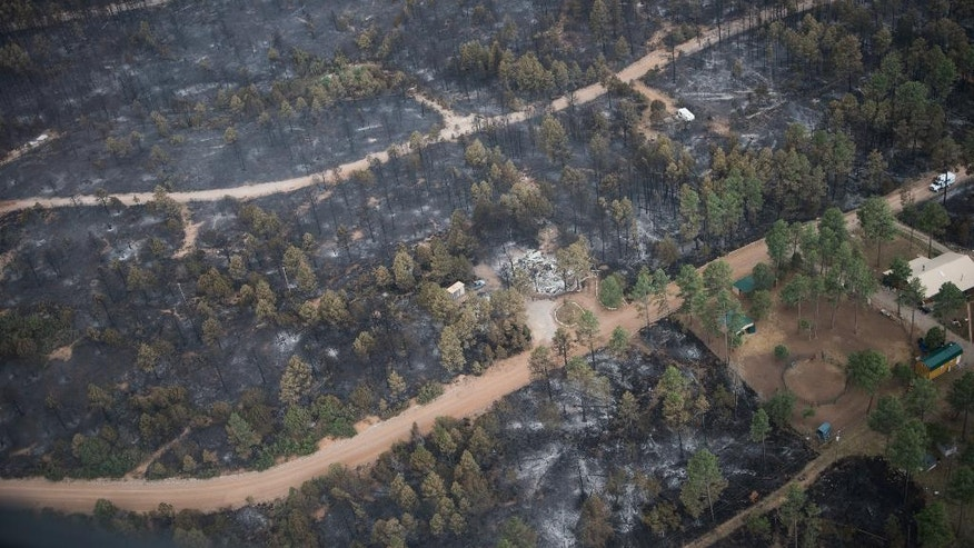 This aerial photo shows the remains of a home that was consumed by a wildfire in the southern New Mexico mountain village of Timberon, Friday, July 15, 2016. New Mexico Gov. Susana Martinez has declared a state of emergency in response to a wildfire in Otero County. Friday afternoon's declaration will enable the county to get additional resources needed to fight the wildfire in Timberon. (Roberto E. Rosales/The Albuquerque Journal via AP, Pool)