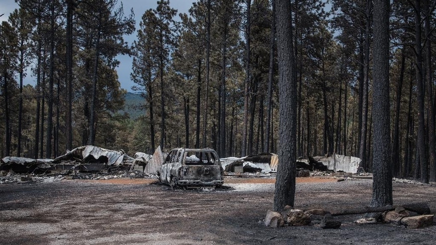A burned out car rests next to the remains of a home after a wildfire in the southern New Mexico mountain village of Timberon, Friday, July 15, 2016. New Mexico Gov. Susana Martinez has declared a state of emergency in response to a wildfire in Otero County. Friday afternoon's declaration will enable the county to get additional resources needed to fight the wildfire in Timberon. (Roberto E. Rosales/The Albuquerque Journal via AP, Pool)