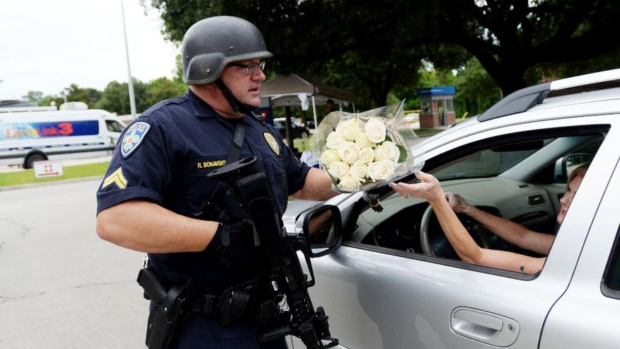 Baton Rouge police officer Randy Bonaventure takes a bouquet of flowers at the Our Lady of the Lake Hospital where the police officers were brought this morning, Sunday, July 17, 2016. Multiple law enforcement officers were killed and wounded Sunday morning in a shooting near a gas station in Baton Rouge. (Henrietta Wildsmith/The Times via AP)