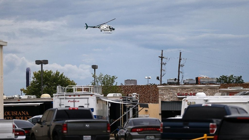 A police helicopter flies over the crime scene where Baton Rouge police were shot, in Baton Rouge, La., Sunday, July 17, 2016. Multiple law enforcement officers were killed and wounded Sunday morning in a shooting near a gas station. (AP Photo/Gerald Herbert)