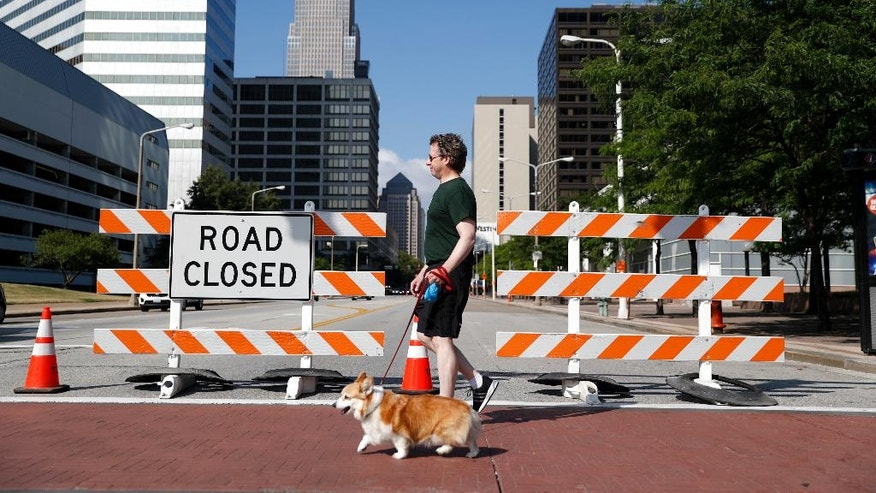 A resident walks near a road closure on Sunday, July 17, 2016, in Cleveland, in preparation for the Republican National Convention that starts Monday. (AP Photo/John Minchillo)