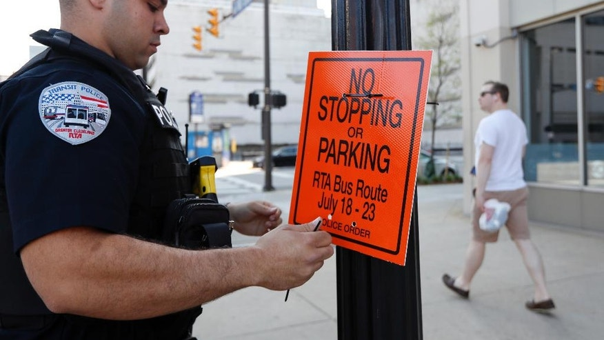 Carlos Cerspo, a Cleveland police officer, hangs a sign warning against stopping or parking, Sunday, July 17, 2016, in Cleveland, in preparation for the Republican National Convention. (AP Photo/John Minchillo)
