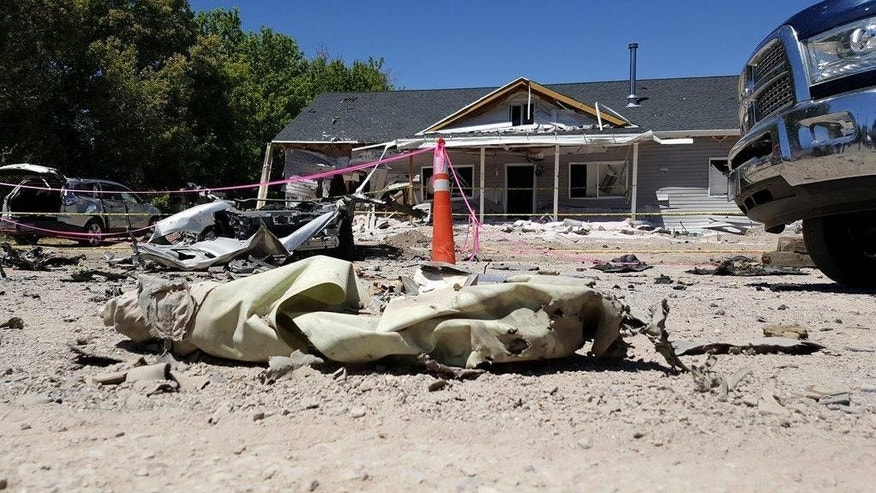 This July 14, 2016 photo provided by Dennis Sanders shows a house in Panaca, Ariz. after it was destroyed by explosives.  Arizona police announced Friday the discovery of improvised bombs and several pounds of explosives found in Kingman, Ariz., in the home and car of a man who traveled to the quiet Nevada town and set off bombs that killed him and showered the community with shrapnel and debris.  (Dennis Sanders via AP)