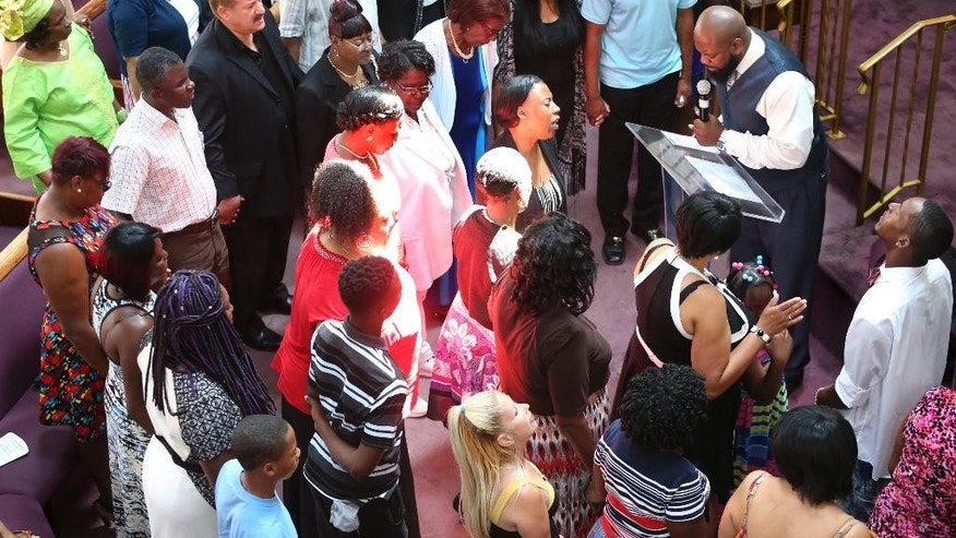 "People pray at New Hope Memorial Baptist church before Gwen Carr, mother of Eric Garner, and Rev. Al Sharpton speak at a service Sunday, July 17, 2016, in Elizabeth, N.J. Two years after the chokehold death of Eric Garner made ""I can't breathe"" a rallying cry for protests over police killings of black men, federal authorities are still grappling with whether to prosecute the white officer seen on a widely watched video wrapping his arm around Garner's neck. (AP Photo/Mel Evans)"